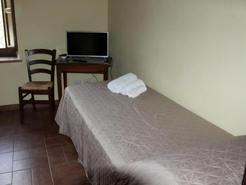 Dormire in Umbria letto e scrivania camera tripla con vista giardino