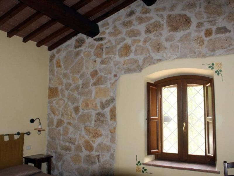 Dormire in Umbria parete in pietra camera tripla con vista giardino